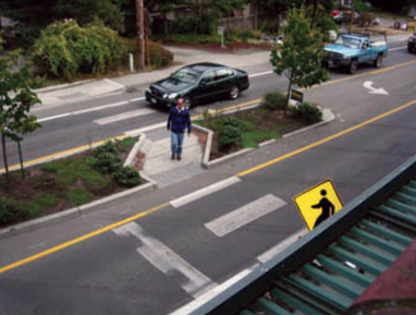 A person waits to cross a narrow road on a well-designed pedestrian-friendly median
